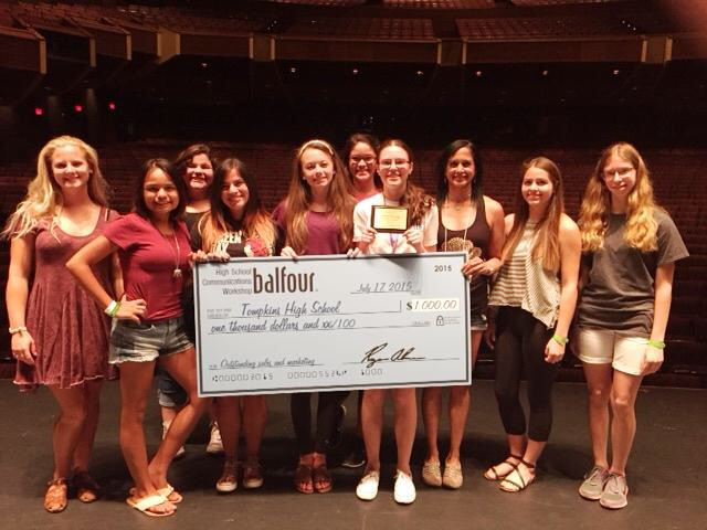 OTHS yearbook, magazine and online newspaper staff members receiving a $1000 check for increasing yearbook sales.