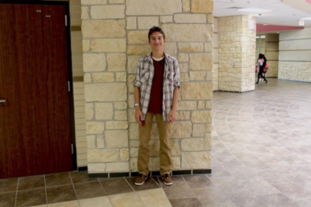 Junior Christopher Hollhumer displaying a fall themed outfit. Hollhumer cleverly pairs the fall colored plaid button up with a red shirt and tan pants.
