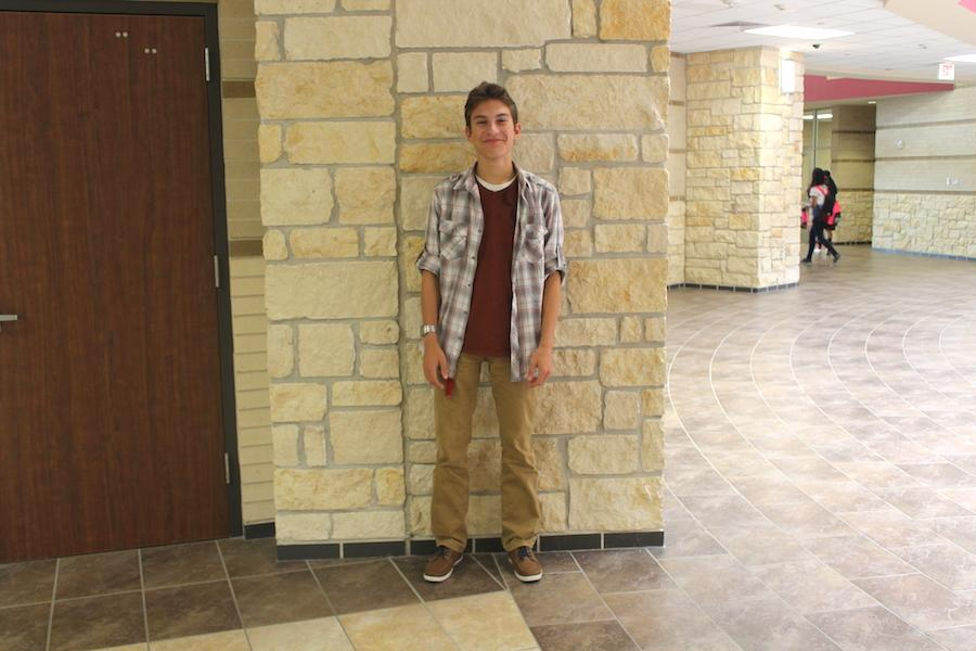 Junior Christopher Hollhumer displays a fall themed outfit. Hollhumer cleverly pairs the fall colored plaid button up with a red shirt and tan pants.